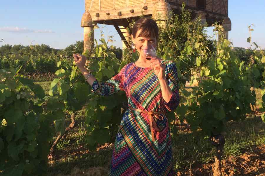 Viktorija Todorovska wine tasting next to grape vines.